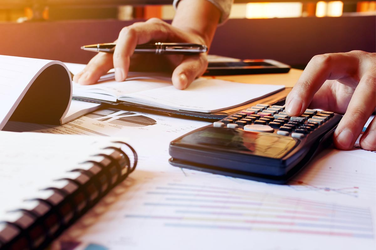 Picture of a person using a calculator to separate their personal and business finances